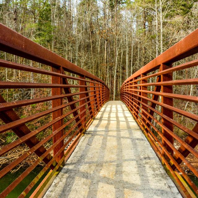"""Colorful red steel pedestrian truss bridge"" stock image"