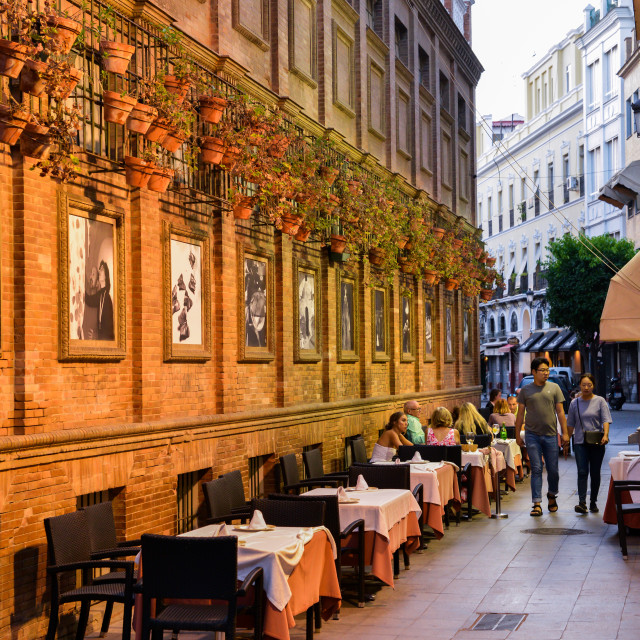 """Romantic outdoors Spanish restaurant with flower pots on wall in the heart of..."" stock image"