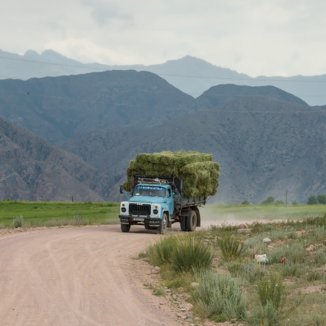 """Old truck carrying a heavy load of hay. Near Bokonbayevo, Kyrgyzstan."" stock image"