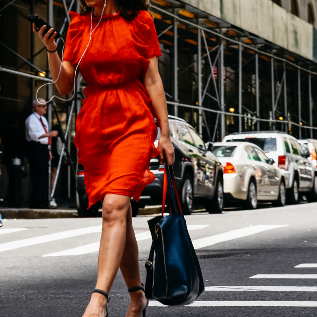 """Woman in red dress with smartphone crossing street in New York"" stock image"