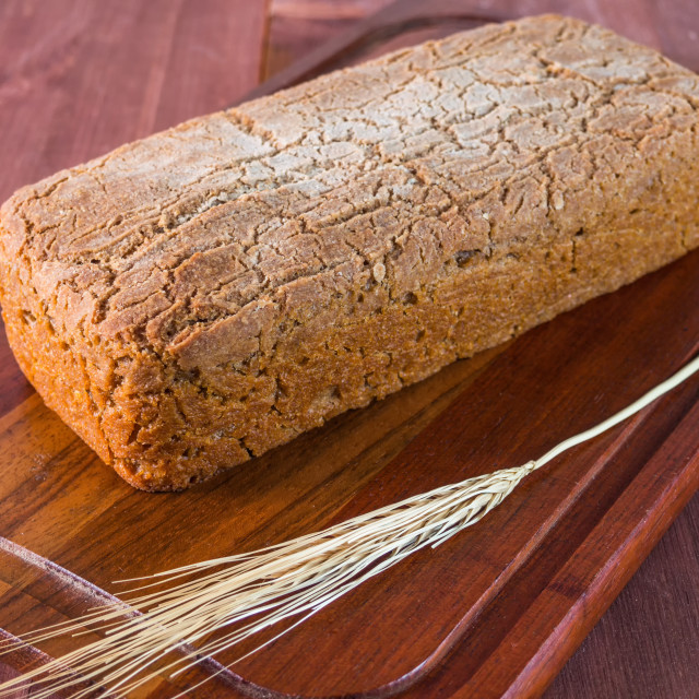 """""""Homemade baked bread and a stalk of wheat on a cutting board"""" stock image"""