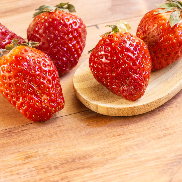 """""""Big juicy strawberries in a wooden spoon on a wooden background"""" stock image"""
