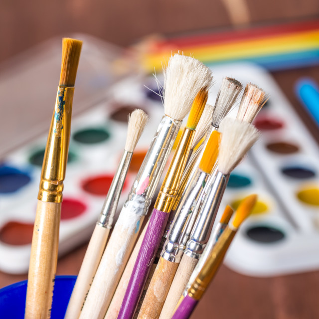 """""""Artistic brushes in a cup close-up against a background of watercolor sets"""" stock image"""