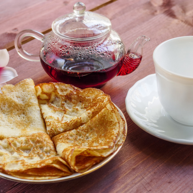 """""""A plate with pancakes and a white cup and a teapot with tea on a wooden table"""" stock image"""