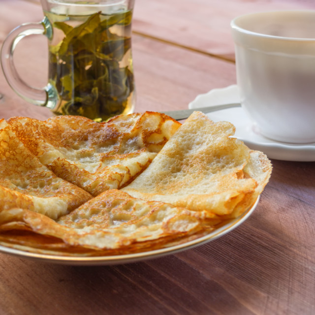 """""""Plate with pancakes, a cup with green Chinese tea on a wooden table"""" stock image"""