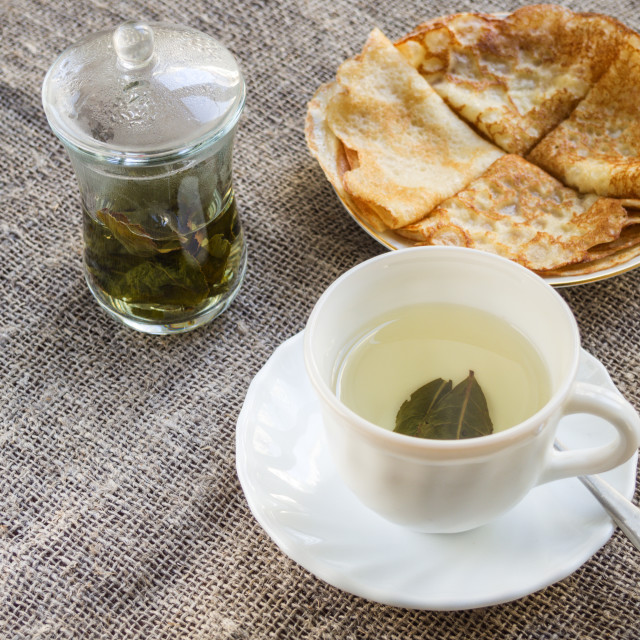 """""""Pancakes and a cup of Chinese green tea on a tablecloth"""" stock image"""