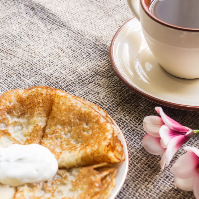 """""""Hot pancakes on a plate with sour cream, a cup with red tea and a glass teapot"""" stock image"""