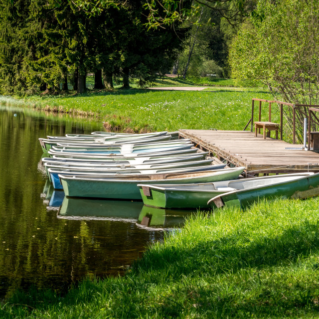 """""""Boats moored on a pier by the lake shore."""" stock image"""