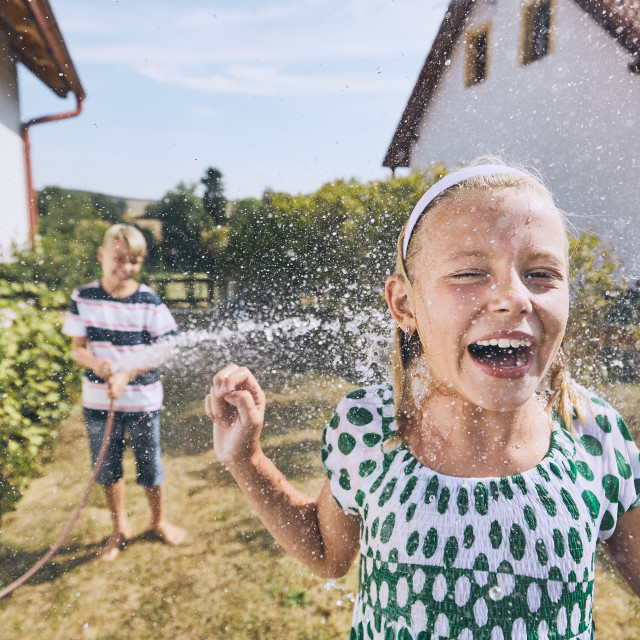 """Children having fun with splashing water"" stock image"