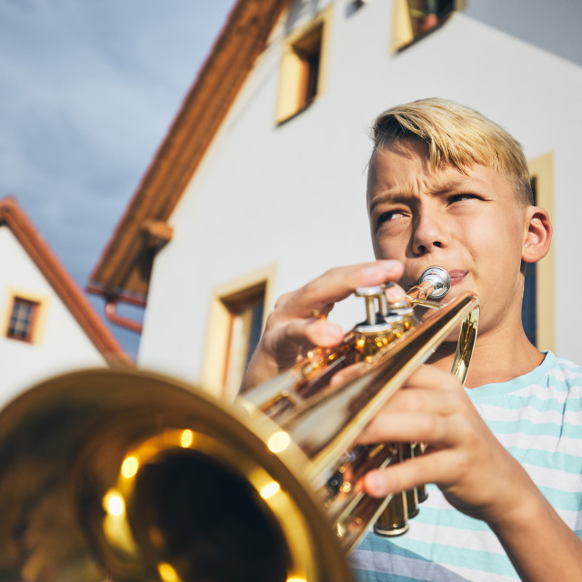 """Little boy playing the trumpet"" stock image"
