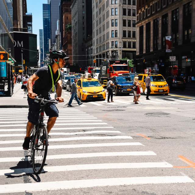 """Cyclist riding by 8th Avenue in New York"" stock image"