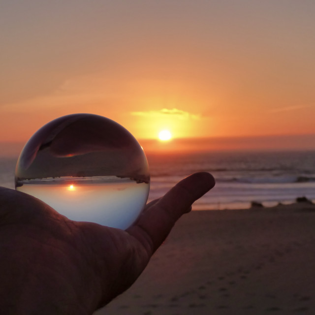 """""""holding a crystal ball at sunset on the beach"""" stock image"""