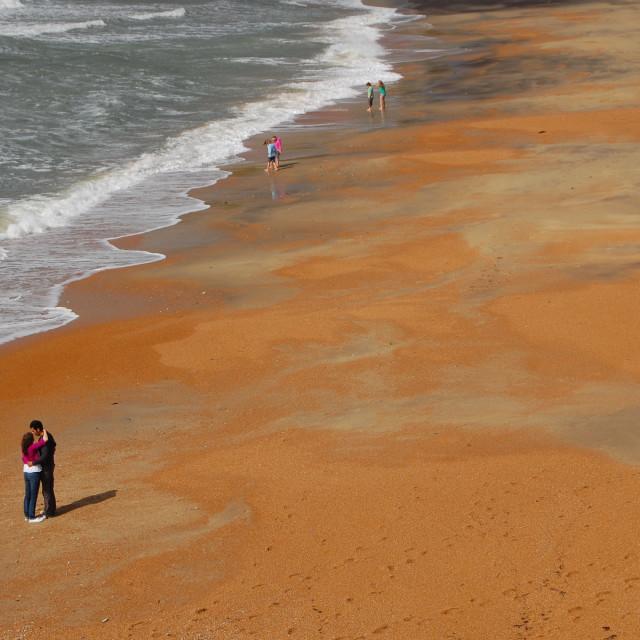 """Embracing couple on Sandy Beach"" stock image"
