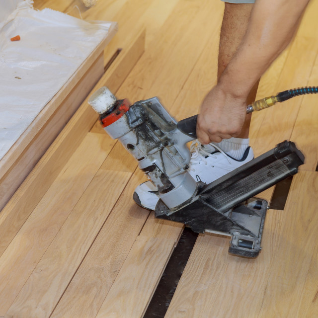 """""""Handyman installing wooden floor in use pneumatic hammer new house"""" stock image"""