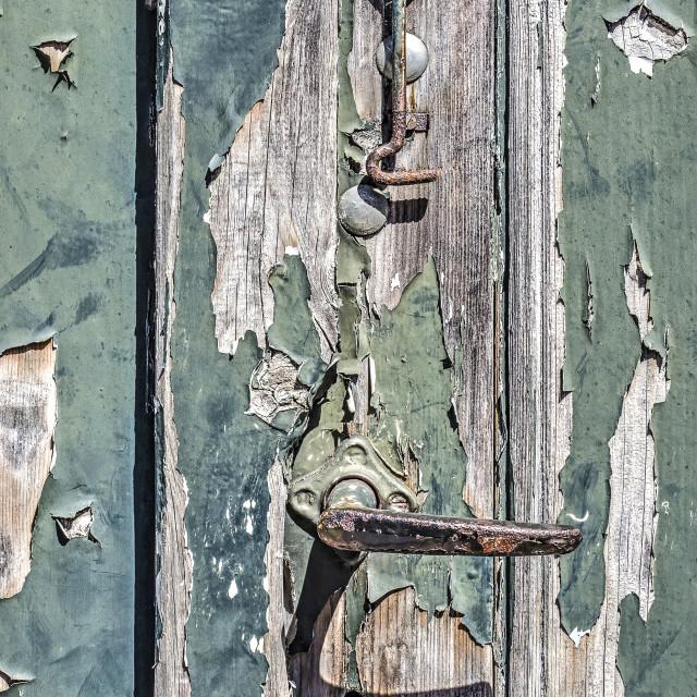 """Rusty door knob on ageing wood"" stock image"