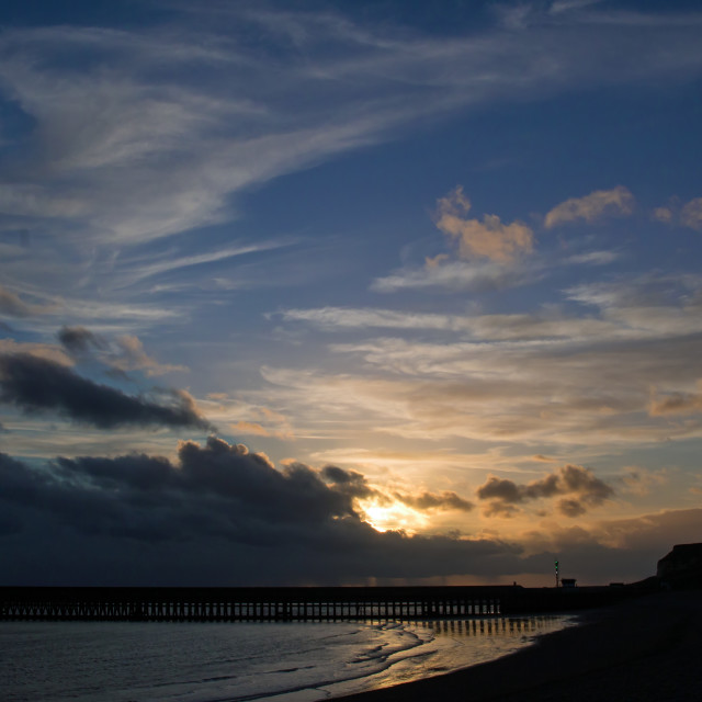"""Setting sun and clouds over Newhaven Harbour in Sussex, England."" stock image"