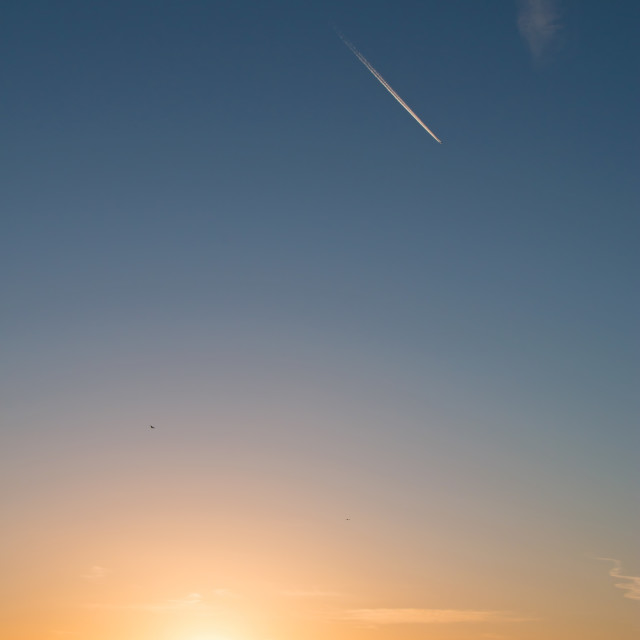 """Sunrise and Plane Trail"" stock image"