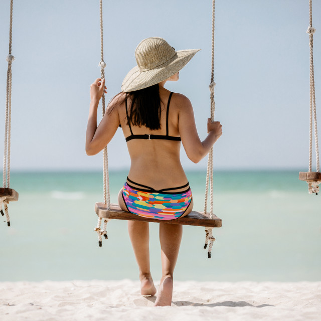 """A female in bikini sits on a swing on the beach"" stock image"