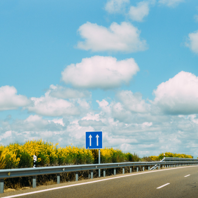 """""""Blue sign pointing up at empty highway with blue sky and fluffly clouds"""" stock image"""