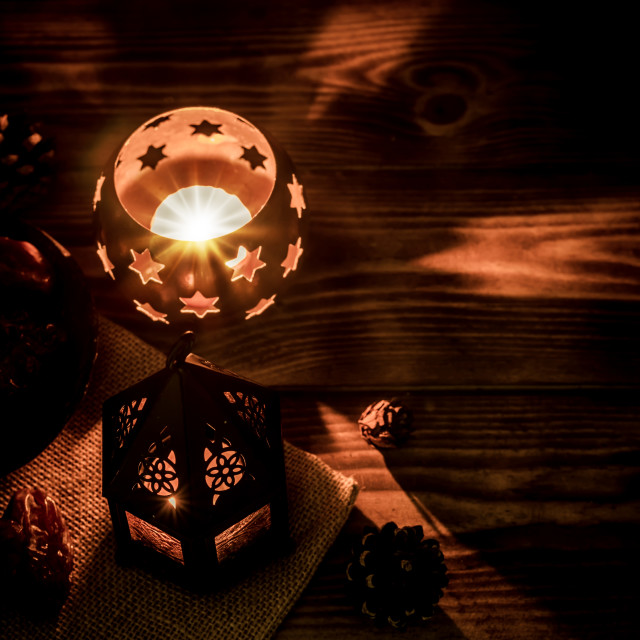 """""""Arabic lantern with candle and date palm fruit at night for Islamic holiday. Muslim holy month Ramadan. The end of Eid and Happy New Year. Copy space on dark background."""" stock image"""