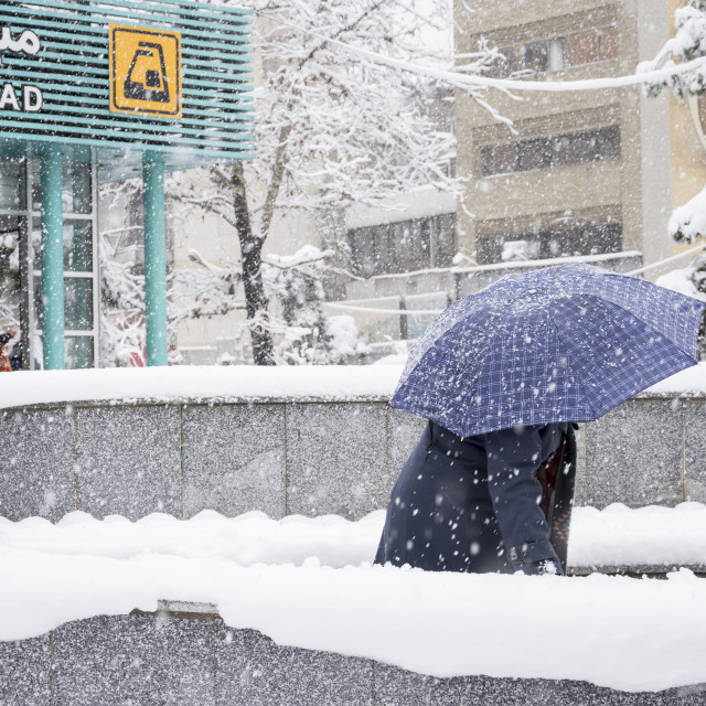 """""""Women comes out from metro station with umbrella in snowy day"""" stock image"""