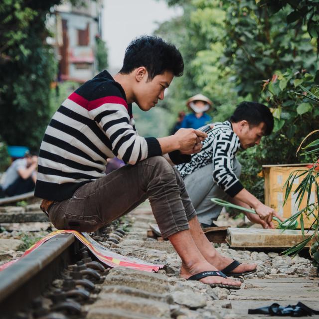 """Man sat on train tracks, Hanoi Old Quarter, Vietnam"" stock image"