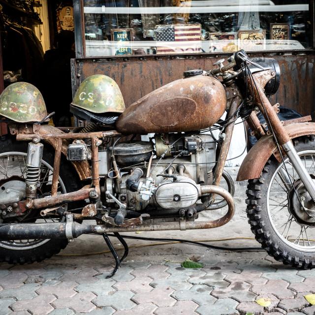 """Old, grungy, military motorbike with helmets, Hanoi, Vietnam"" stock image"