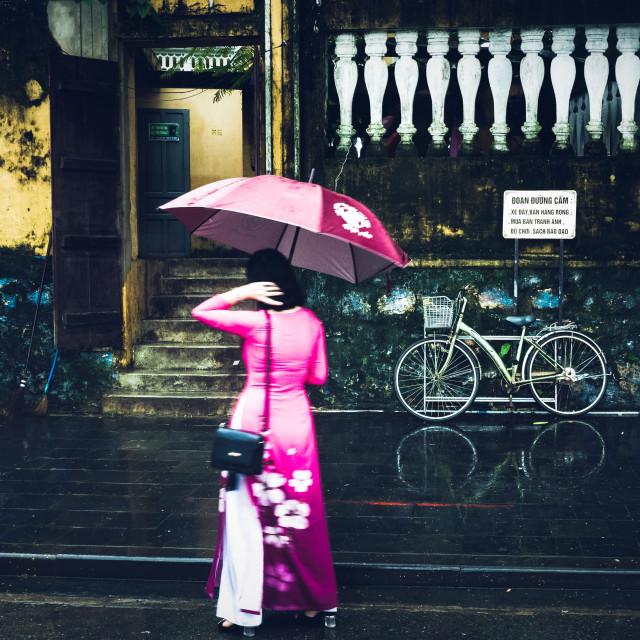 """Lady in silk dress holding an umbrella, Hội An, Vietnam"" stock image"
