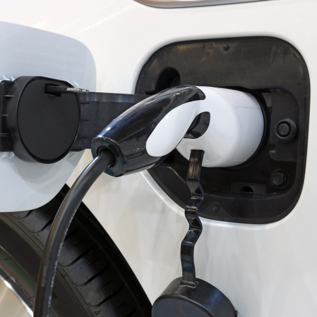 """electric car is charging close up"" stock image"
