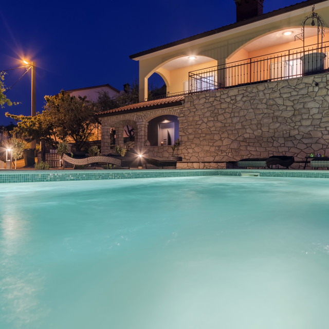 """Holiday home with swimming pool at night"" stock image"