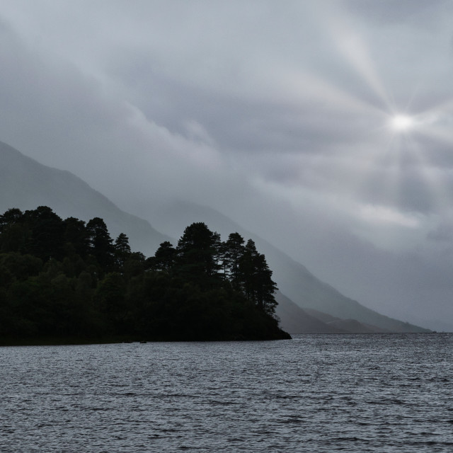 """Ray of Sunshine on a Moody Loch"" stock image"