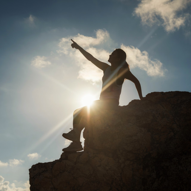 """woman point finger to sky at hill peak"" stock image"