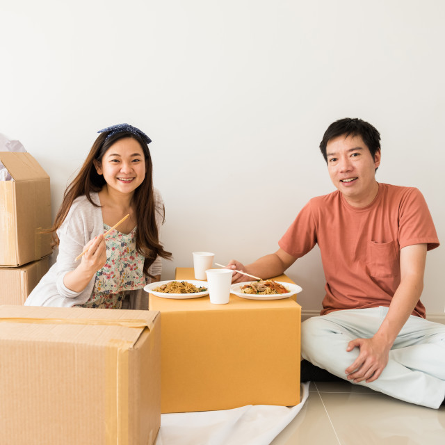 """Happy couple eat noodle on carboard box at new house"" stock image"