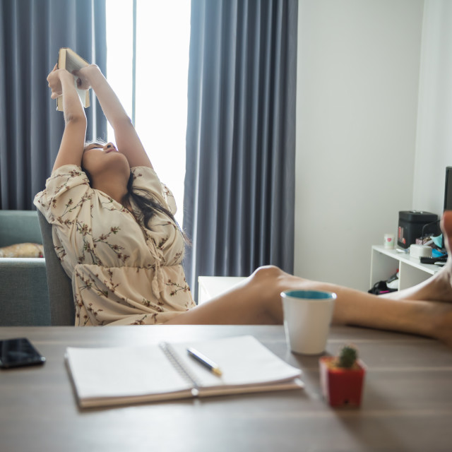 """Woman stretch body during reading book"" stock image"