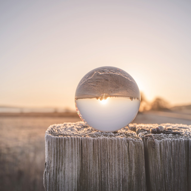 """""""Glass orb on a wooden post in the sunrise"""" stock image"""