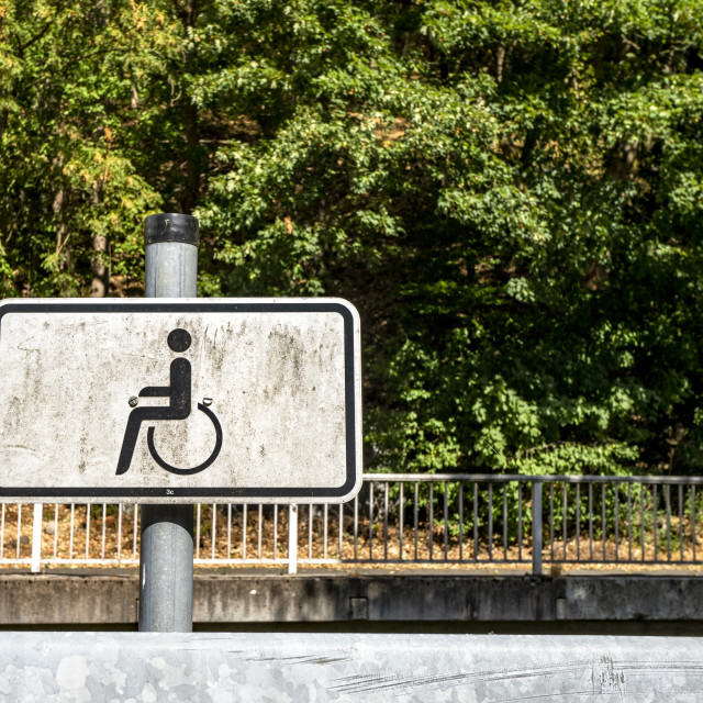 """Dirty handicap sign with a wheel chair"" stock image"