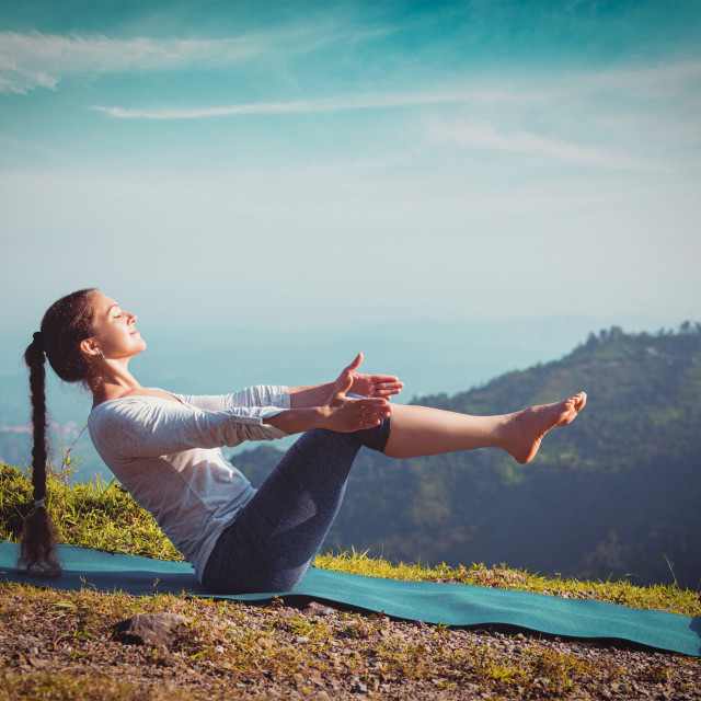 """Woman doing Ashtanga Vinyasa Yoga asana Navasana - boat pose"" stock image"