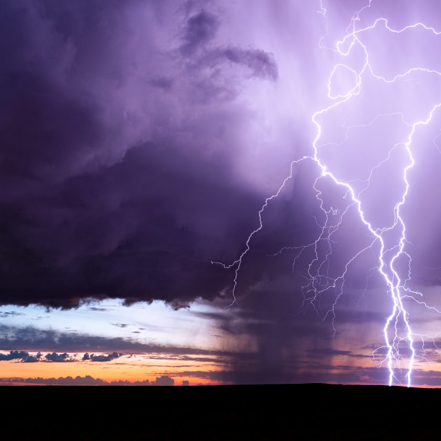 """Lightning bolt strike from a thunderstorm at sunset"" stock image"