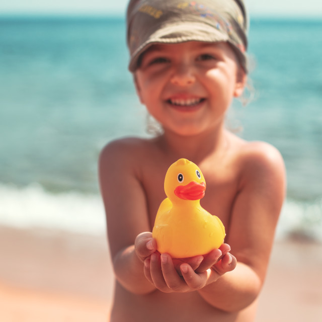 """Little girl holding in hands yellow rubber duck toy on the beach"" stock image"