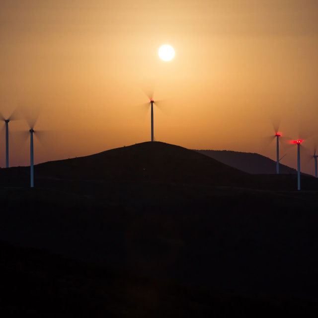 """Silhouette of windmills with a sunset"" stock image"