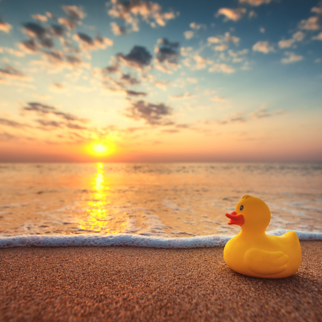 """Yellow rubber duck toy on the beach during beautiful sea sunrise"" stock image"