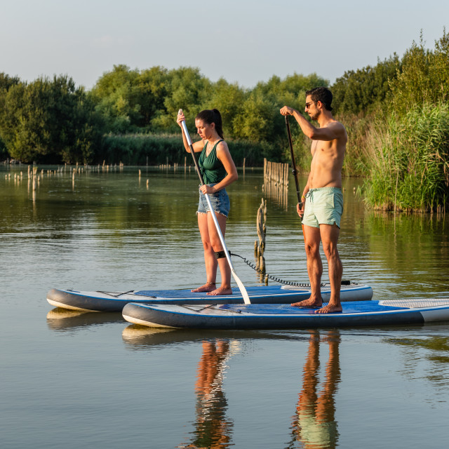 """Man and woman stand up paddleboarding"" stock image"