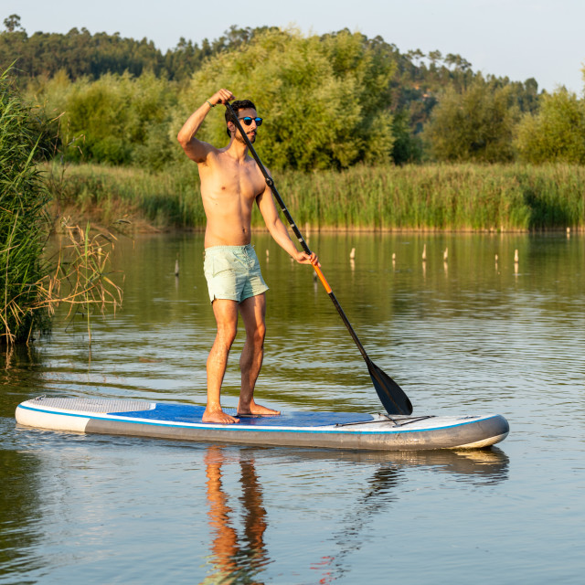 """Man stand up paddleboarding"" stock image"