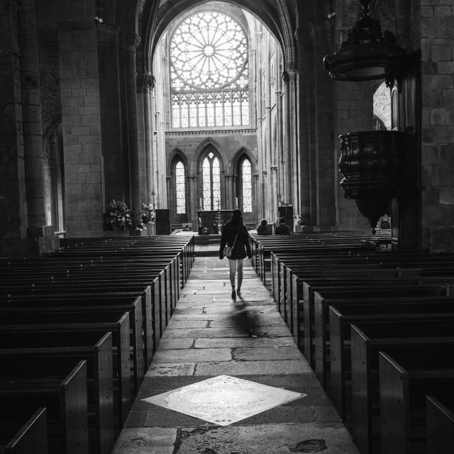"""A woman walking down the aisle of a dark cathedral approach the altar"" stock image"
