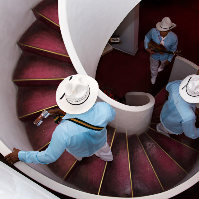 """A Mexican trio going up a spiral staircase to play music"" stock image"