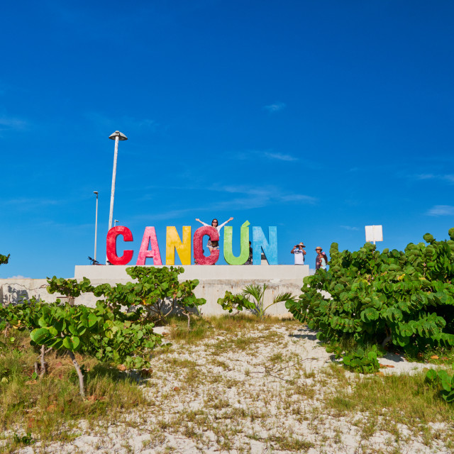 """Girl lifts her arms up in front of Cancun sign, Playa Delfines, Mexico, in September 7 , 2018"" stock image"
