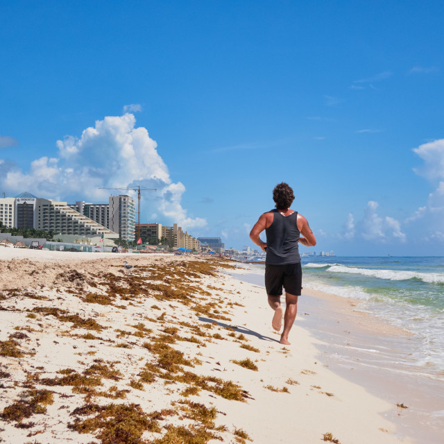 """Young man jogging in tropical beach"" stock image"
