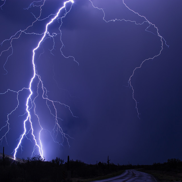 """""""Lightning bolt striking a mountain during a thunderstorm."""" stock image"""