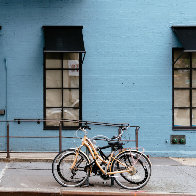 """Bicycles parked against blue painted brick facade"" stock image"