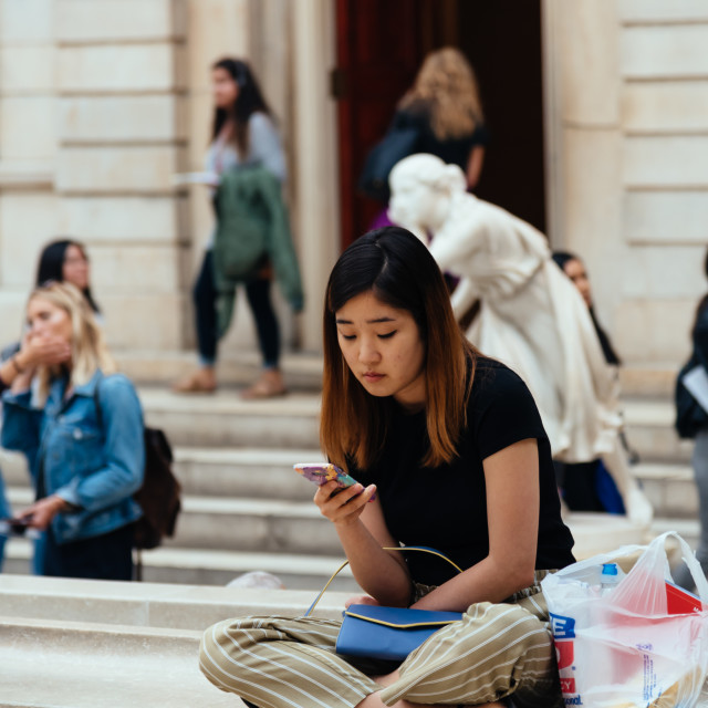 """Young woman sitting on museum surfing the internet"" stock image"